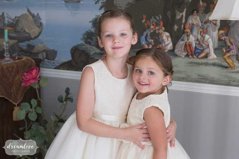 Adorable flower girls smile for a photo in Manchester-by-the-Sea, MA.