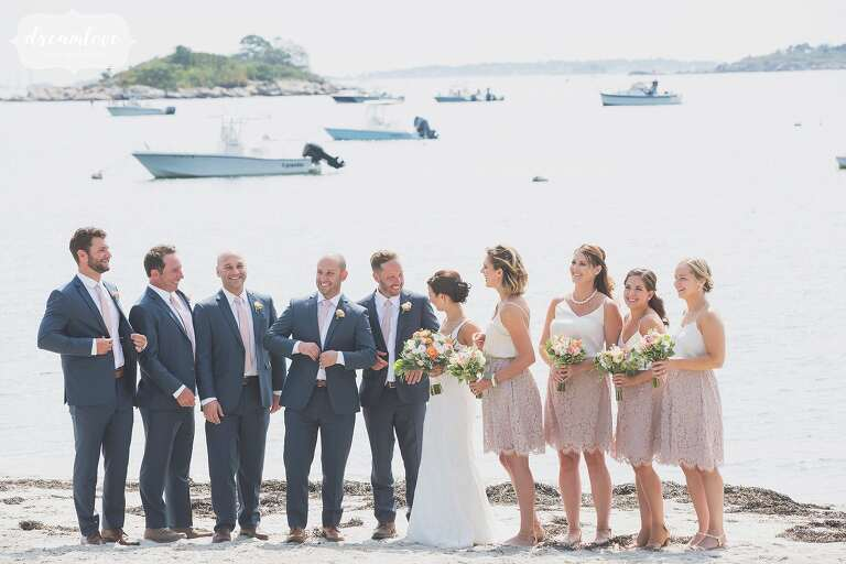The wedding party poses on Singing Beach in BHLDN skirts and white tops on the north shore of MA.