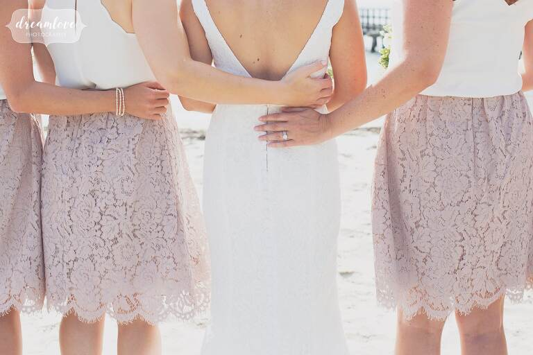 Fine art wedding photo of the bridesmaids with their arms around the bride in Manchester by the Sea, MA.