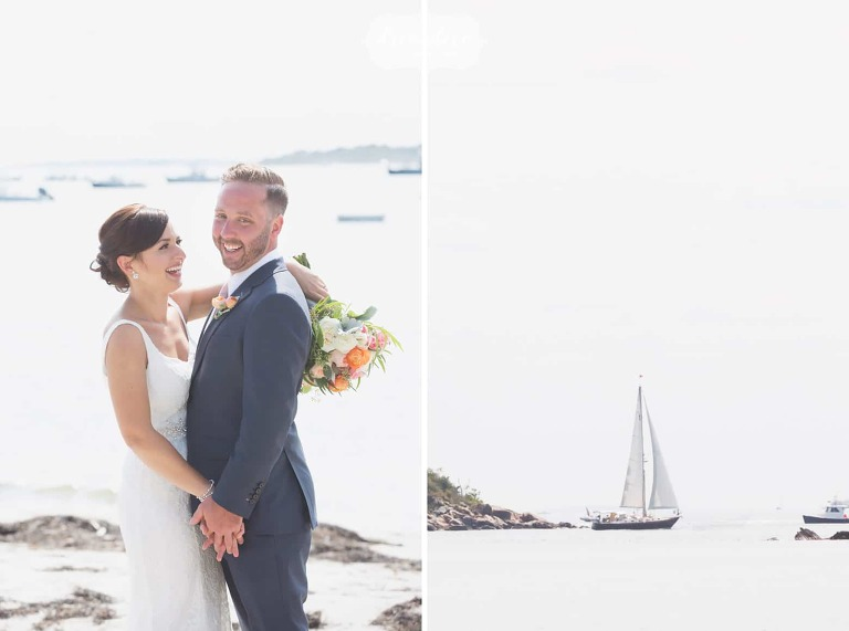 Bride and groom with a sailboat behind them on the beach in Manchester by the Sea.