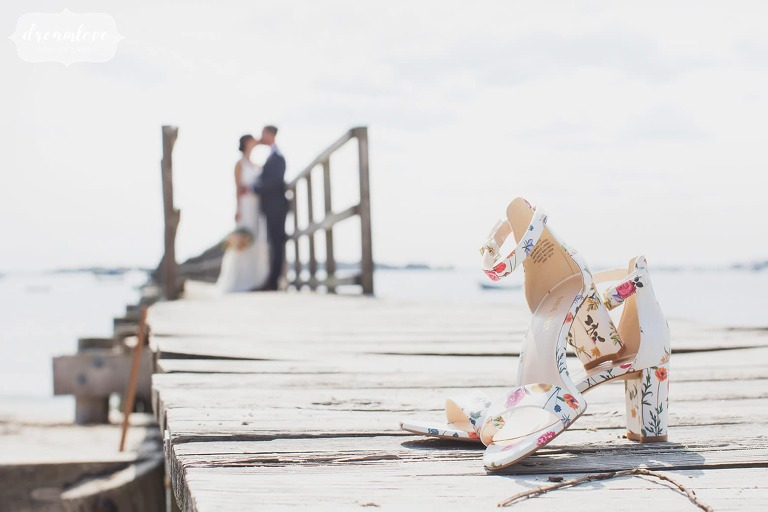 Unique wedding photo of the bride's shoes in the foreground with bride and groom on the pier in Manchester, MA.