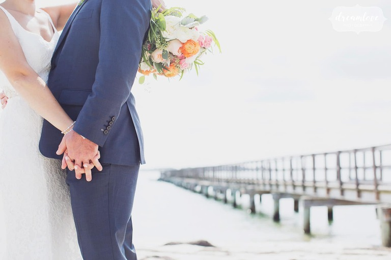 Romantic wedding photography of the couple holding hands on the pier in Manchester by the Sea, MA.