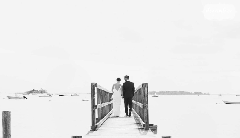 Black and white wedding photography of the bride and groom walking down the pier in Manchester, MA.