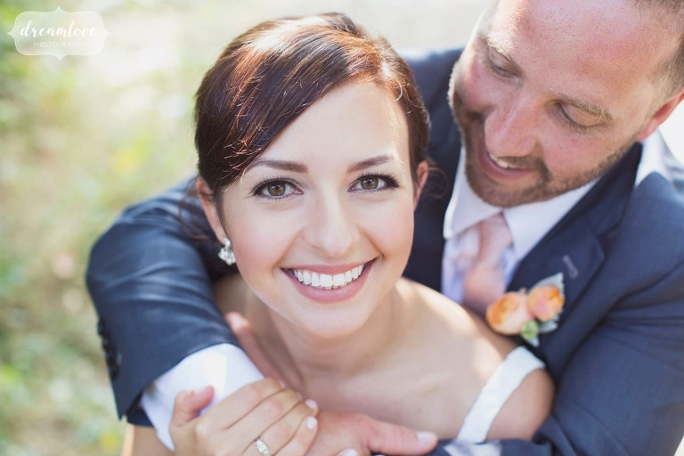 Close up photo of the bride smiling with the groom wrapping his arms around her in MA.