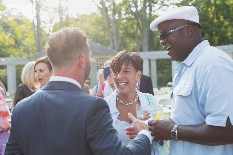 Happy wedding photography of the guests mingling in Manchester by the Sea backyard wedding.