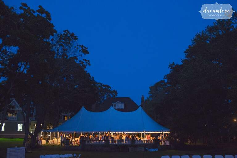 The sailcloth reception tent is bathed in blue light for this backyard wedding near Singing Beach.