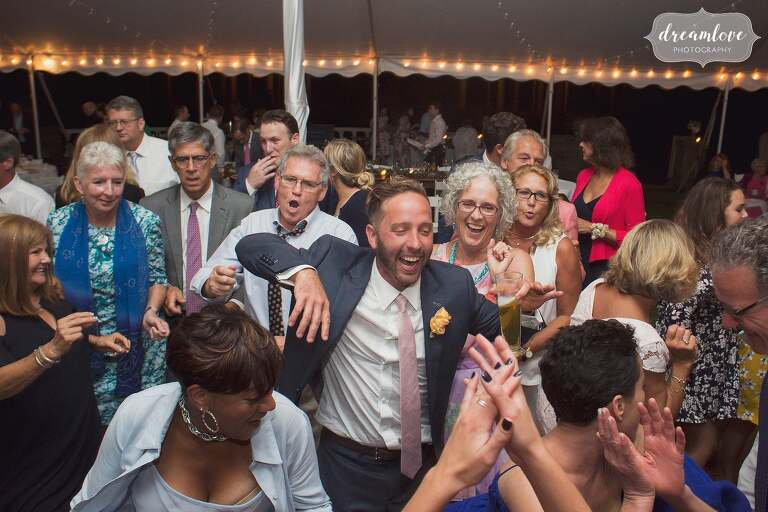 The groom laughing in the center of the dance floor in Manchester by the Sea.