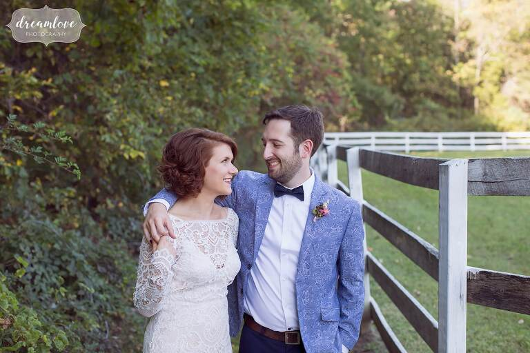 The groom puts his arm around the bride while standing next to a horse fence at this Barn at Liberty Farms wedding venue in upstate NY