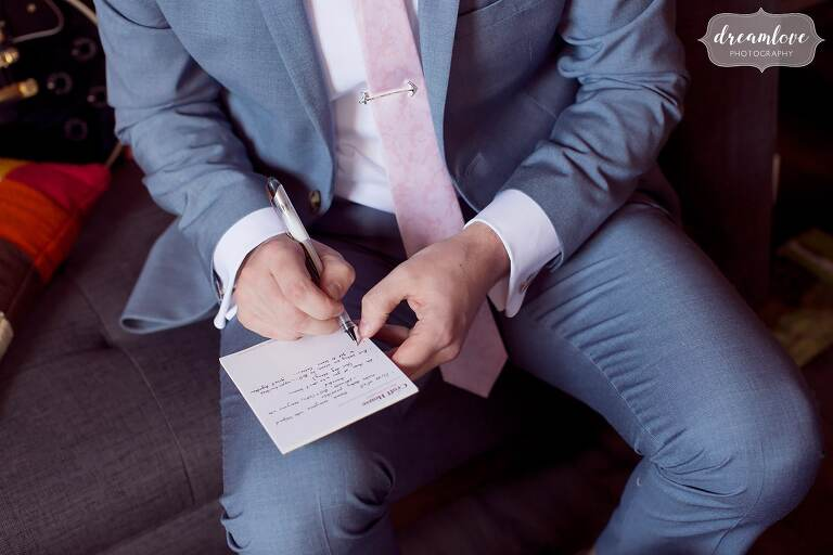 The groomsman writes his speech in pastel suit and tie at the Barn at Liberty Farm wedding venue near Hudson NY.