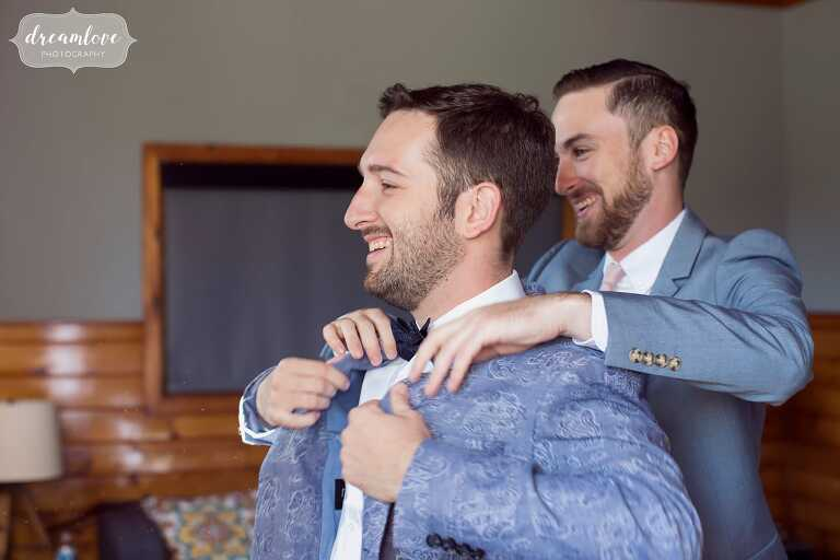 The groom in a paisley suit jacket gets dressed before his barn wedding in the Hudson Valley.