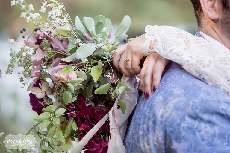 Romantic wedding photography of the bride's arms around her groom's neck with her stunning flowerkraut bouquet with fall colors.