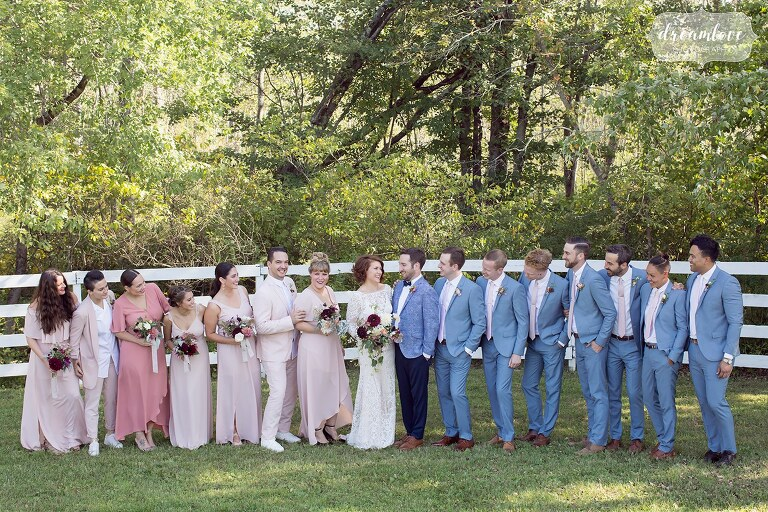 The wedding party poses in the horse pasture in pastel pink bridesmaid dresses and pale blue suits at the Barn at Liberty Farms.