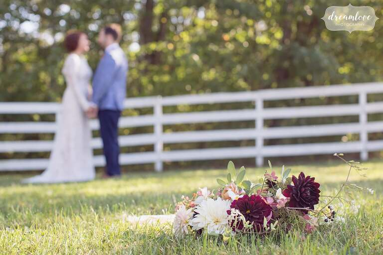 A fall wedding bouquet on the ground with the bride and groom blurry in the background at the Barn at Liberty Farms.
