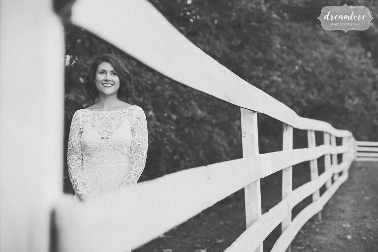 The bride framed in a white fence while wearing a 1940's hairstyle and looked stunning at this horse wedding venue in the Hudson Valley.