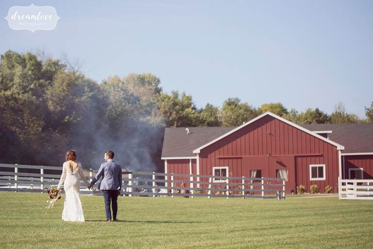 The bride and groom hold hands while walking back to their red reception barn in the Hudson Valley.