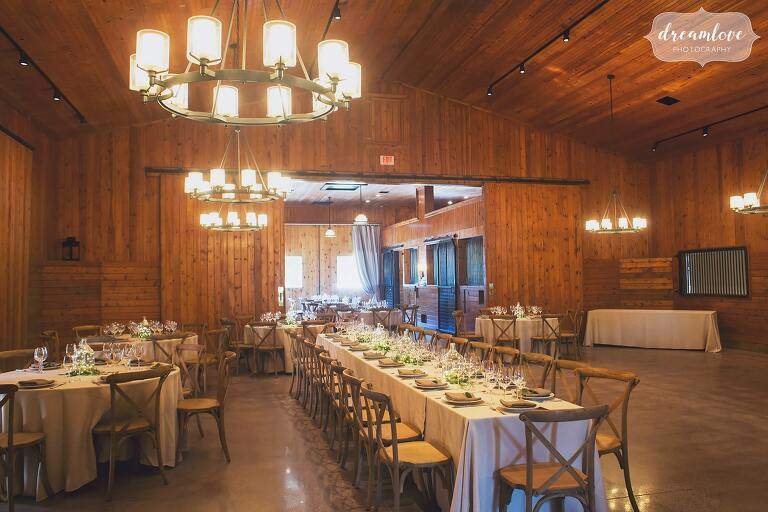 Family style dinner tables are set up with candle chandeliers for this Barn at Liberty Farms wedding in Ghent.