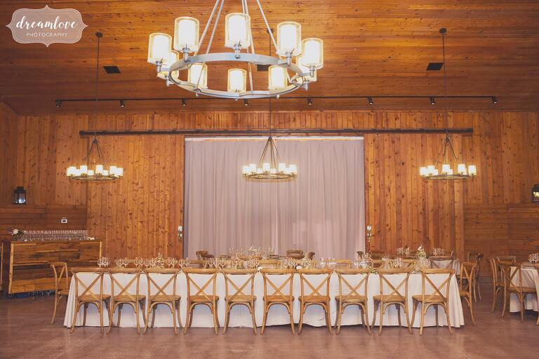 Family style table is set up with wooden cafe chairs at the rustic Barn at Liberty Farms.