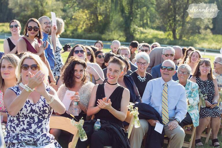 Wedding guests smile during this outdoor ceremony in September at the Barn at Liberty Farms.