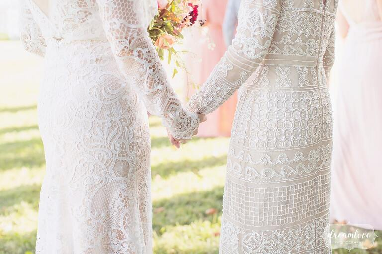 The bride and her mother hold hands while wearing embroidered lace and beaded dresses for a September wedding in Ghent.