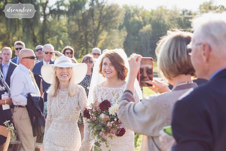 The bride walks down the aisle with her mother in a designer embroidered wedding dress at the Liberty Farms.