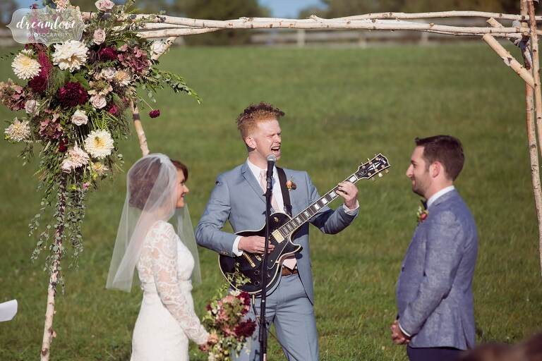 A groomsmen plays the guitar during a musical wedding ceremony at the Barn at Liberty Farms.