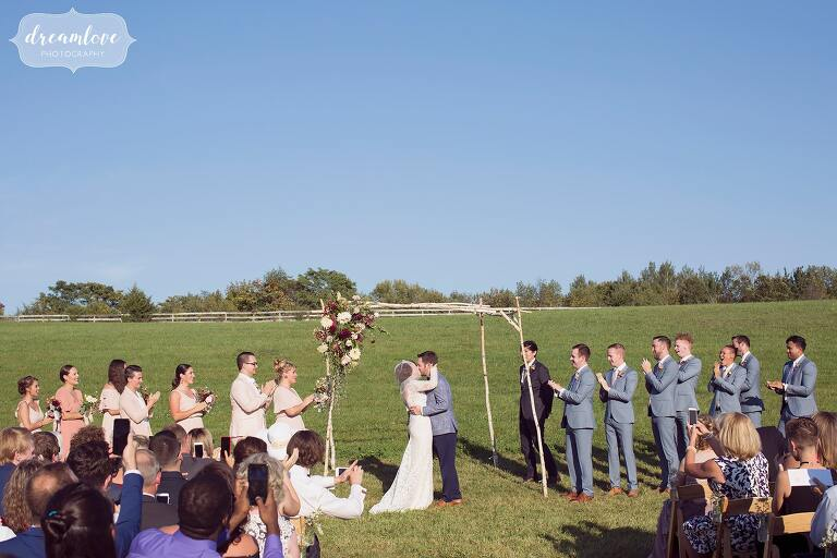 The bride and groom kiss under a handmade birch wood arbor at the Barn at Liberty Farms.