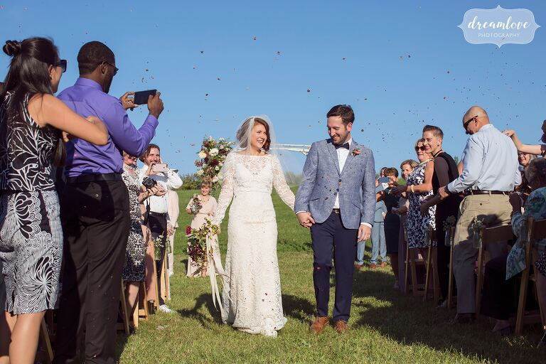 Guests throw flower petals into the air over the happy bride and groom as they exit their ceremony in upstate NY.