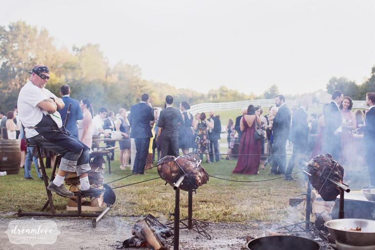 A man pedals meat on the rotisserie for the Fire Roasted catering company at this Hudson Valley wedding.