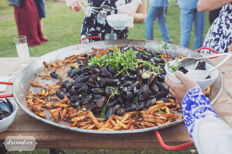 Mussels and fries are presented by the Fire Roasted Catering company at this Barn at Liberty Farms wedding in the Hudson Valley.