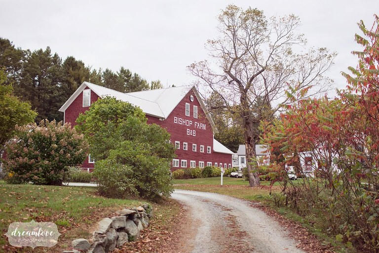 The old red dairy barn at the Bishop Farm barn wedding in the white mountains venue is pictured with a stone rock wall.