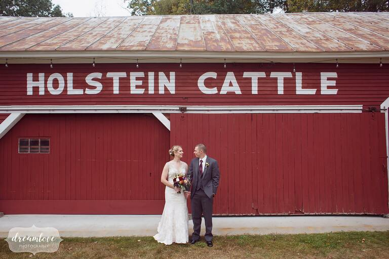 The bride and groom pose in front of a red barn that says Holstein Cattle. This venue used to be a dairy barn in NH.
