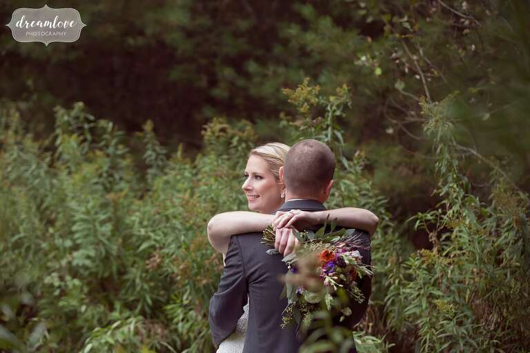 The bride and groom are surrounded by the woods in this soft light wedding photo at Bishop Farm.