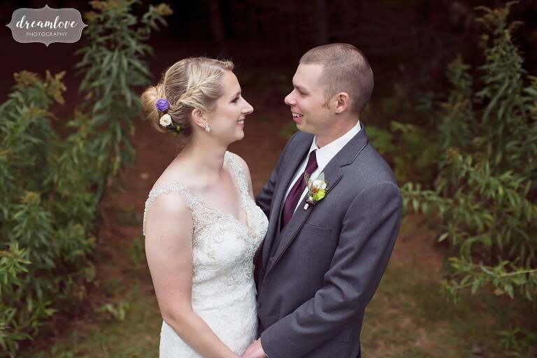 Bride and groom pose in the forest at this NH barn wedding at Bishop Farm.