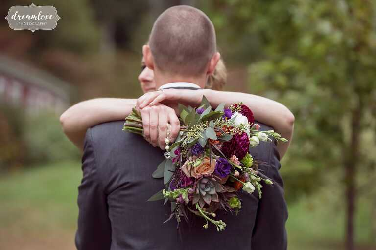 The bride wraps her arms around the groom with her fall wedding bouquet at Bishop Farm.