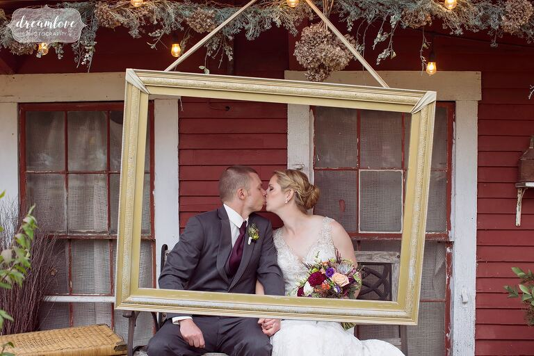 The bride and groom kiss on the porch at Bishop Farm behind a hanging picture frame.