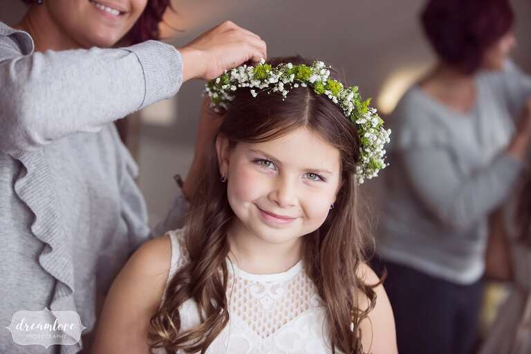 A wholesome flower girl poses with her baby's breath crown at the Bishop Farm.