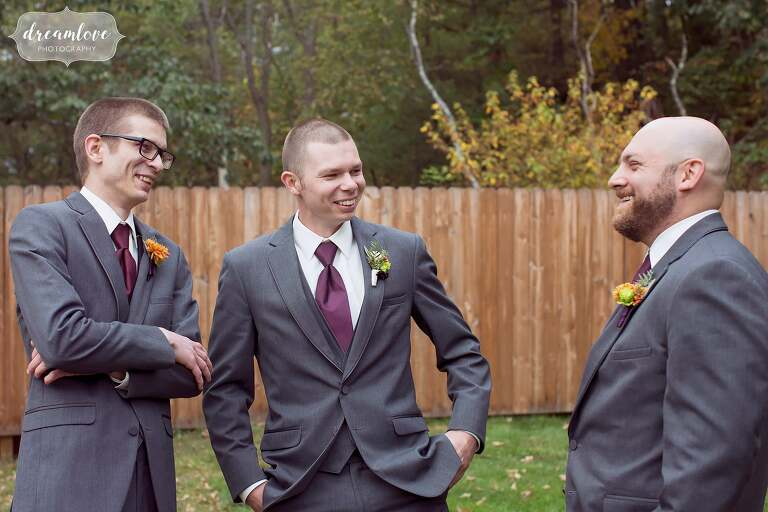 The groom laughs with his friends in this candid wedding photo before his barn ceremony at Bishop Farm.
