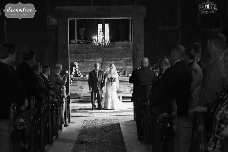 The bride and her father stand in the barn doorway at the Bishop Farm before the wedding ceremony.