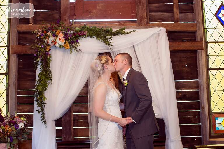 The bride and groom kiss at the end of their ceremony inside of the barn at Bishop Farm in NH.
