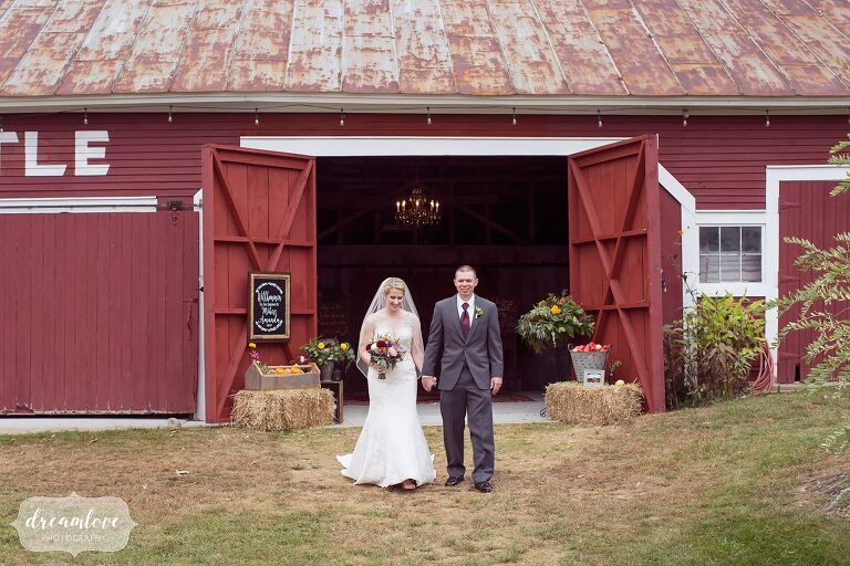 The bride and groom exit their ceremony in the red barn at Bishop Farm.