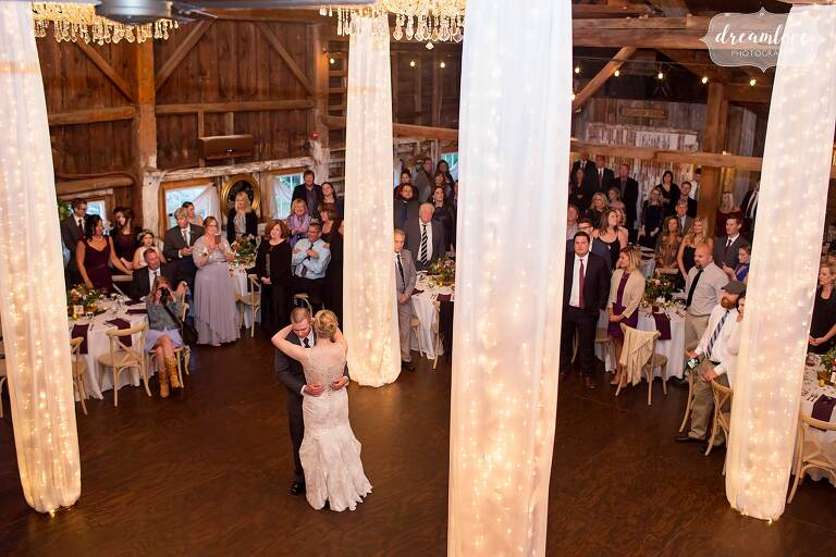 This shabby chic barn wedding reception had draped fabric from twinkle light chandeliers! From a wedding at the Bishop Farm barn venue in NH.