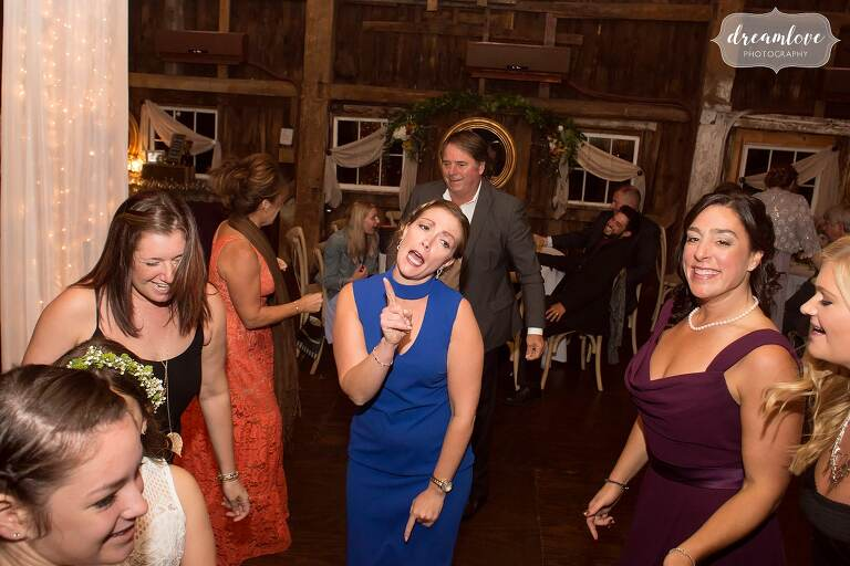 A wedding guest in a blue dress pretends to sing on the dance floor at Bishop Farm.