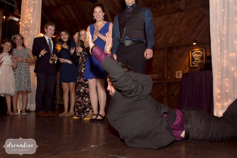 Documentary wedding photography of a wedding guest doing the worm on the dance floor at Bishop Farm.