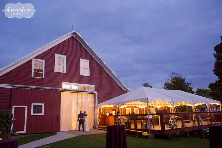 The bride and groom walk through the draped curtains at the end of their barn wedding in the white mountains at Bishop Farm barn wedding venue in NH at the end of the night.