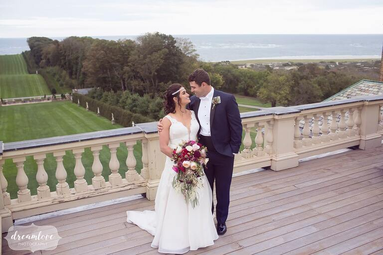 Bride and groom stand on the roof of the Crane Estate, a storybook wedding venue on the ocean just north of Boston, MA.