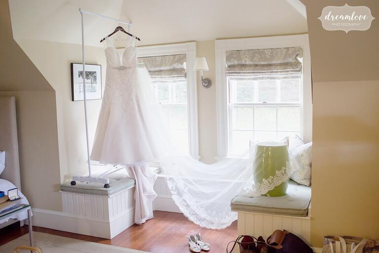 The wedding dress is hung from the ceiling with a long train and veil at the Castle Hill Inn at the Crane Estate.