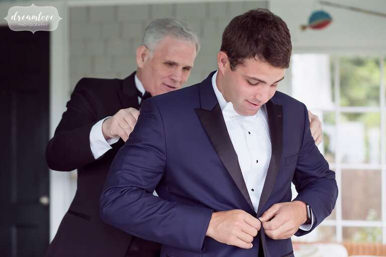 The groom's father helps his son with his tuxedo jacket at the Crane Estate in MA.