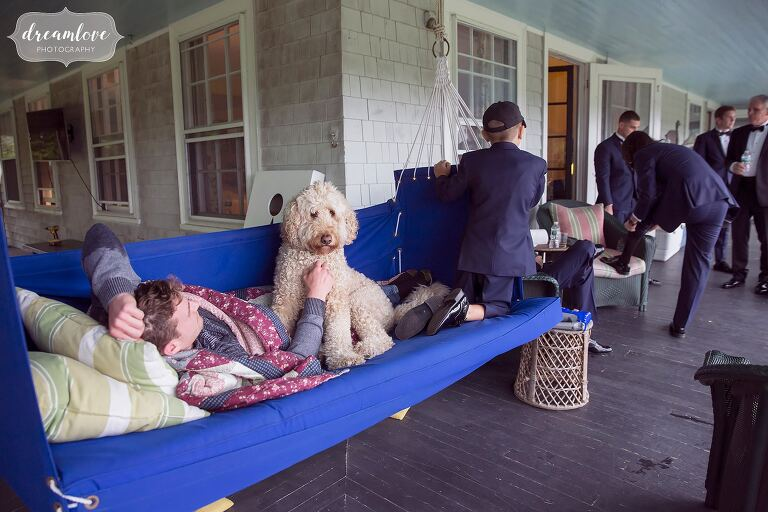 A goldendoodle dog cuddles with a groomsman before this Crane Estate wedding in MA.