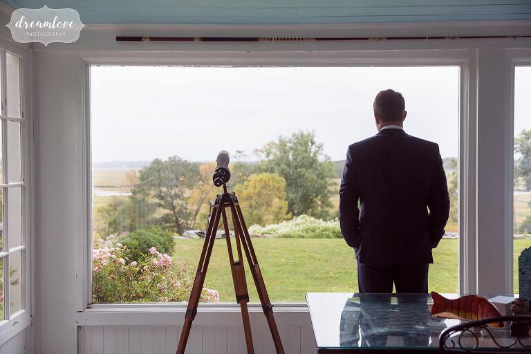 The groom looks out of the window at the Crane Estate salt marshes of Ipswich, MA.