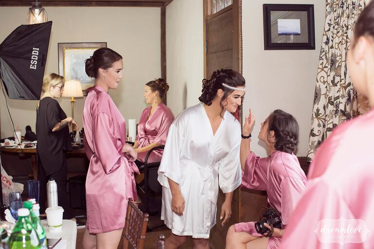 The bride and her bridesmaids in pink robes get ready for the wedding day in the Crane Estate tavern.